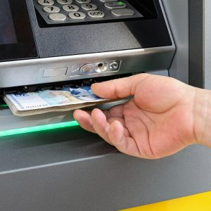 Caucasian man hand taking bulgarian levs from ATM. Receive money at a cash machine outdoors. ATM cash withdrawal. Close-up.